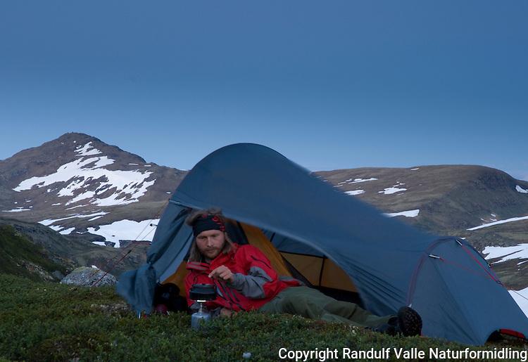 Mann koker kaffe i teltåpning med fjellet Forollhogna i bakgrunnen --- Man making coffe in camp with mountain Forollhogna in the background