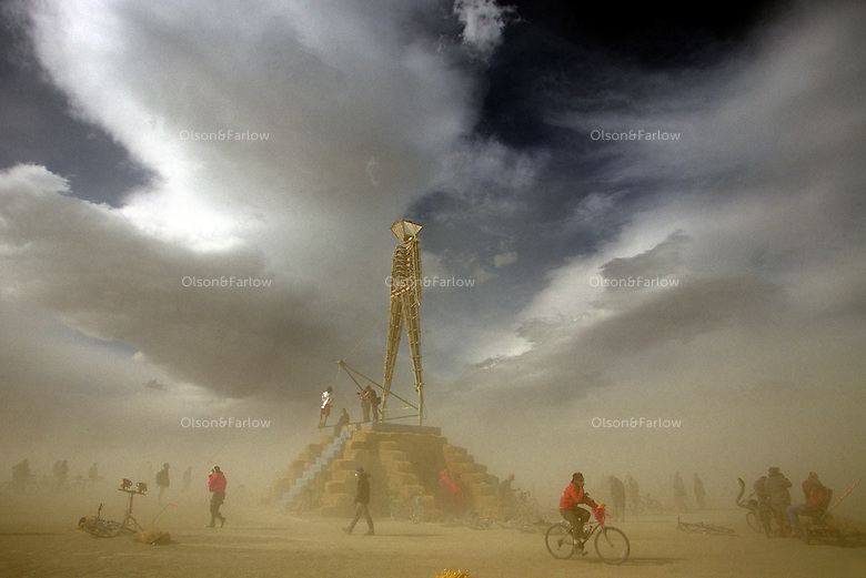 Harsh desert winds swirl around a 70-foot plywood and neon figure before it is ignited for the Burning Man Festival.  The Black Rock Desert in northwestern Nevada's Conservation area, becomes one of Nevada's largest cities, attracting tens of thousand of revelers celebrating art and counter-culture experience.