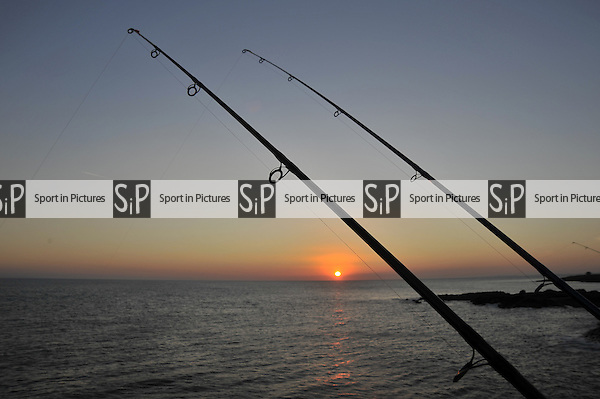 Fishing rods at sunset at the end of the Porthcawl harbour wall. South Wales. UK. 30/09/2015. MANDATORY Credit Garry Bowden/Sportinpictures - NO UNAUTHORISED USE - 07837 394578