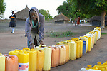A girl lines up jerry cans before dawn in the Rhino Refugee Camp in northern Uganda. As of April 2017, the camp held almost 87,000 refugees from South Sudan, and more people were arriving daily. About 1.8 million people have fled South Sudan since civil war broke out there at the end of 2013. About 900,000 have sought refuge in Uganda. <br /> <br /> Because water pumps in the camp are solar-powered, water can only be obtained during daylight hours. Refugees will therefore line up their jerry cans overnight in order to be among the first to get water in the morning.<br /> <br /> The Global Health Program of the United Methodist Church has supported work to improve access to safe drinking water in the camp.