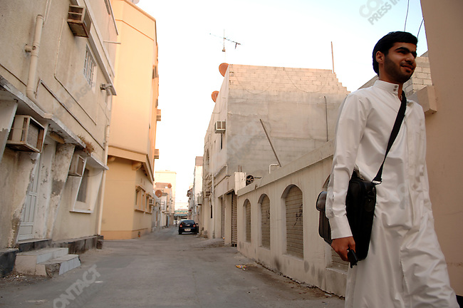 Ali Abdulemam, founder of Bahrainonline.com walking down the street to his house on the outskirts of Manama, the capital of Bahrain, December 16, 2005.