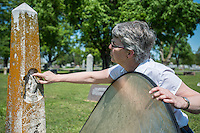 NWA Democrat-Gazette/ANTHONY REYES &bull; @NWATONYR<br /> Abby Burnett, author, checks for damage on a tomestone Tuesday, April 21, 2015 at Bluff Cemetery in Springdale. Burnett will sometimes use a reflector to fill in shadows on tombstones when she takes pictures.