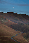 Barren mountains with road at night under moon in winter