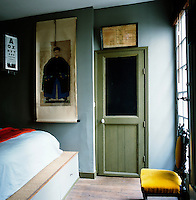A snug blue-painted bedroom has a double bed on a raised platform