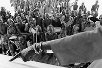 Sudan. Southern part. Bahr El Ghazal. Panthou. Dinka tribe area. Children at school listen to the class while the teacher's hand shows the writing words on a backboard made of a recycled board of wood. © 1998 Didier Ruef
