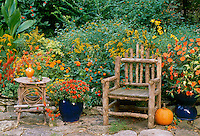 Gorgeous stone patio with rustic handbuilt chair and table with orange flowers in beds and pots