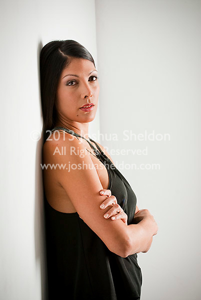 Young Hispanic woman leaning on wall