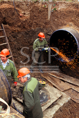 Slovakia. Three men wearing orange hard hats in an excavated hole working on a large gas pipeline using an angle grinder.