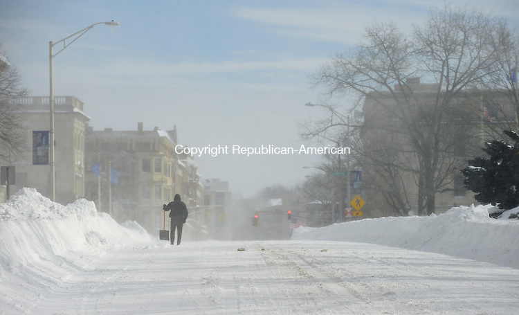 WATERBURY, CT - 9 February 2013-020913EC02--   A man with a shovel walks along Grand Street in Waterbury Saturday.  The city received at least 2 feet of snow from the blizzard. Erin Covey Republican-American.