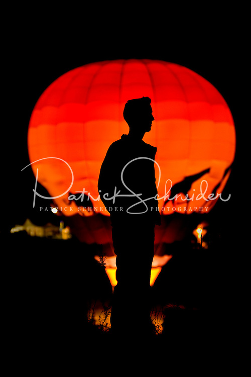 An attendee of the Carolina BalloonFest is silhouetted against a glowing balloon during the October 2008 event. The event is held each fall in Statesville, NC.