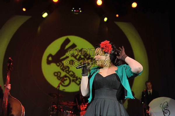 Caro Emerald (Caroline Esmeralda van der Leeuw).performing live in concert, Shepherd's Bush Empire, London, England..13th December 2011.on stage gig performance music half length black dress green jacket gloves flower in hair red singing hand arm profile  .CAP/MAR.© Martin Harris/Capital Pictures.