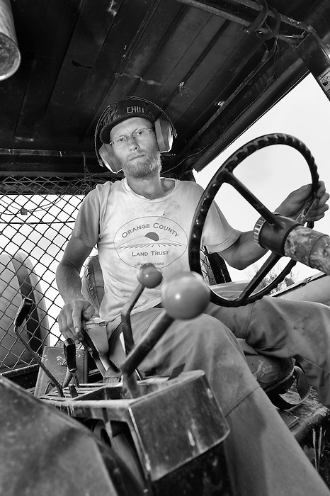 A farmer inside the cab of farm machinery