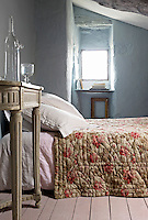 In this attic bedroom the bedside table and rose-patterned quilt are both flea-market finds