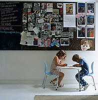 Ellie and Joe sit at a table in a corner of the kitchen beneath a blackboard covered in family pictures