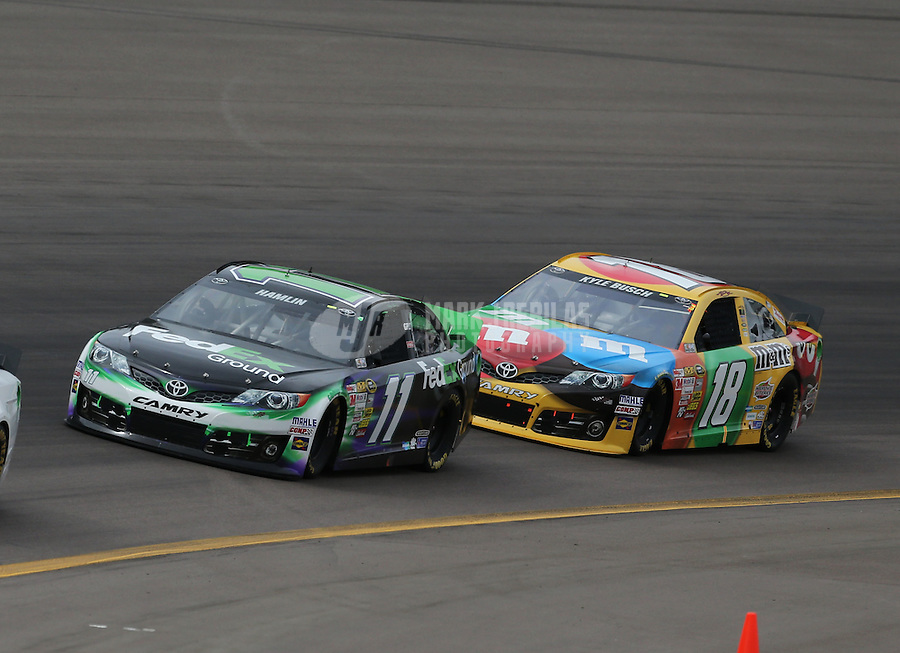 Mar. 3, 2013; Avondale, AZ, USA; NASCAR Sprint Cup Series driver Denny Hamlin (11) leads Kyle Busch (18) during the Subway Fresh Fit 500 at Phoenix International Raceway. Mandatory Credit: Mark J. Rebilas-