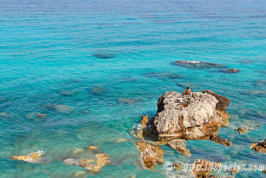 A Fisherman on the rocks of Pefkoulia in Lefkada, Greece