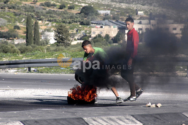 A Palestinian protester burns a tire during clashes with Israeli security forces at Hawwara military checkpoint near the West Bank city of Nablus on February 26, 2013. Increased protests in the West Bank after the killing of a Palestinian Prisoner Arafat Jaradat, 30, whose death in an Israeli jail on 23 February sparked riots across the Israeli-occupied West Bank. Palestinians claim he died of torture. Israel says the initial autopsy could not determine the cause of death and further tests were needed. Photo by Nedal Eshtayah