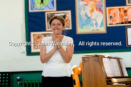 Teacher applauds after concert for parents, Open Day at State Junior School..