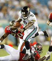 Jacksonville Jaguar quarterback David Garrard (#9) eludes a pair of Tampa bay Buccaneer defenders during an NFL preseason game in Jacksonville, FL on Friday, August 15, 2002.  Tampa bay won the game 20 to 0.(Photo by Brian Cleary/ www.bcpix.com )