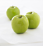 Three Granny Smith green apples on a white background.