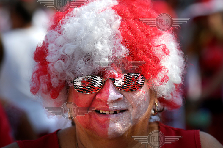 A man wearing a red and white wig, the colours of the Gibraltan flag, during celebrations on Gibraltar National Day. He also has sunglasses embossed with the Gibraltan flag on its lenses.