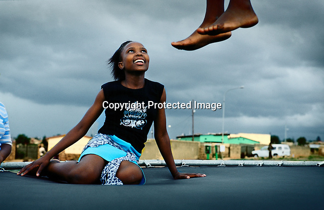 SOWETO, SOUTH AFRICA MARCH 10: Children play on a trampoline on March 10, 2005 in Soweto, Johannesburg, South Africa. Soweto is South Africa?s largest township and it was founded about one hundred years to make housing available for black people south west of downtown Johannesburg. The estimated population is between 2-3 million. Many key events during the Apartheid struggle unfolded here, and the most known is the student uprisings in June 1976, where thousands of students took to the streets to protest after being forced to study the Afrikaans language at school. Soweto today is a mix of old housing and newly constructed townhouses. A new hungry black middle-class is growing steadily. Most residents work in Johannesburg but the last years many shopping malls has been built, and people are starting to spend their money in Soweto. (Photo by Per-Anders Pettersson)