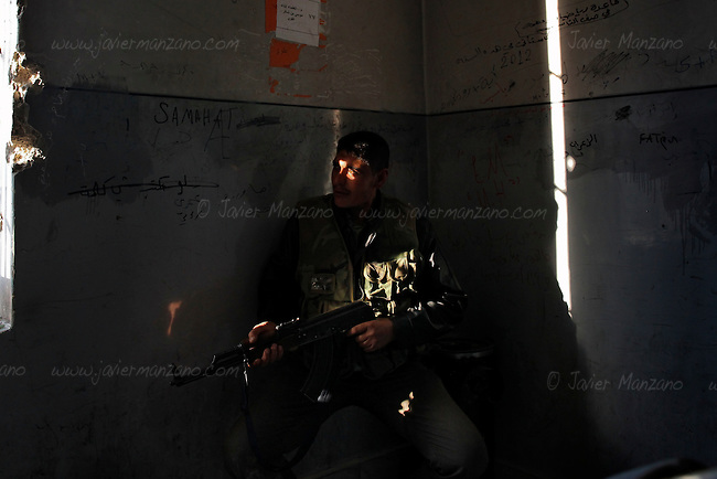 A Free Syria Army soldier prepares to fire at government troops from his base in an abandoned school in the Bustan Al-Basha neighborhood of Aleppo on the last day of a U.N. negotiated seize fire that began on the first day of the Muslim holiday of Eid. Both sides exchanged small arms fire as the regime fired mortars throughout the day on several sectors of the city - the kurdish neighborhood of Ashrafya was also bombed by regime jets on October 29, 2012, following an FSA incursion in the district on Saturday...© Javier Manzano...