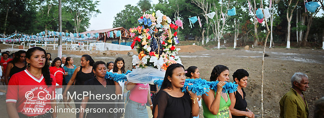 Villagers carrying a staue of the Black Madonna through Fordlandia during an annual festival celebration. This village was one of a number on the banks of the Tapajos river which saw investment in services such as electricity and running water. Access to the village which lay in the heart of the Amazonian rainforest basin was still by unpaved dirt roads from Highway BR163.