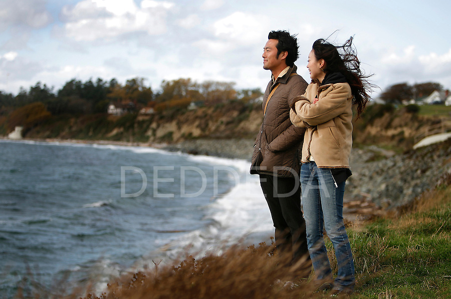 Tatsuya Hikawa and Kazne Fukui look out over the Juan de Fuca Straight during strong coastal winds in Victoria Wednesday. Photo assignment for the Globe and Mail national newspaper in Canada.