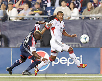 D.C. United defender Ethan White (15) works to clear ball as New England Revolution forward Dimitry Imbongo (92) defends. In a Major League Soccer (MLS) match, the New England Revolution (blue) defeated D.C. United (white), 2-1, at Gillette Stadium on September 21, 2013.