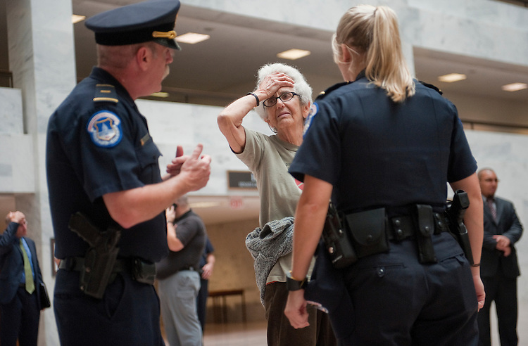 UNITED STATES - OCTOBER 11:  A protester talks to Capitol Police before being arrested in the atrium of Hart Building after a demonstration by many groups including Occupy DC and Code Pink, who expressed their displeasure about issues such as the war in Afghanistan, health care coverage, and the state of the U.S. economy, among other complaints.  (Photo By Tom Williams/Roll Call)