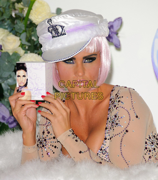 KATIE PRICE aka JORDAN.launches her new perfume 'Precious Love' at The Worx, London, England, UK, November 17th, 2010..half length beige pink purple leotard embellished jewel jewelled gem encrusted wig hair  cleavage white cap hat make-up lipstick eyeshadow red  nails nail varnish polish .CAP/CJ.©Chris Joseph/Capital Pictures.