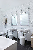 A pair of sinks in an ensuite bathroom clad with white wall tiles and a whimiscally patterned wallpaper