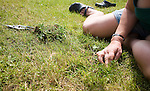 Woman using her hand to pull weeds from her grass lawn, UK