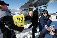 Volunteer load handlers help pilot Greg Miller load his Cessna 180 with Heet and other supplies at the Willow airport during the first day of flying straw, musher's dog food bags and people food & gear out to checkpoints south of the Alaska Range.  Heet is used by mushers as fuel to heat their dog water and food.  Saturday Feb. 21, 2009  Iditarod 2009