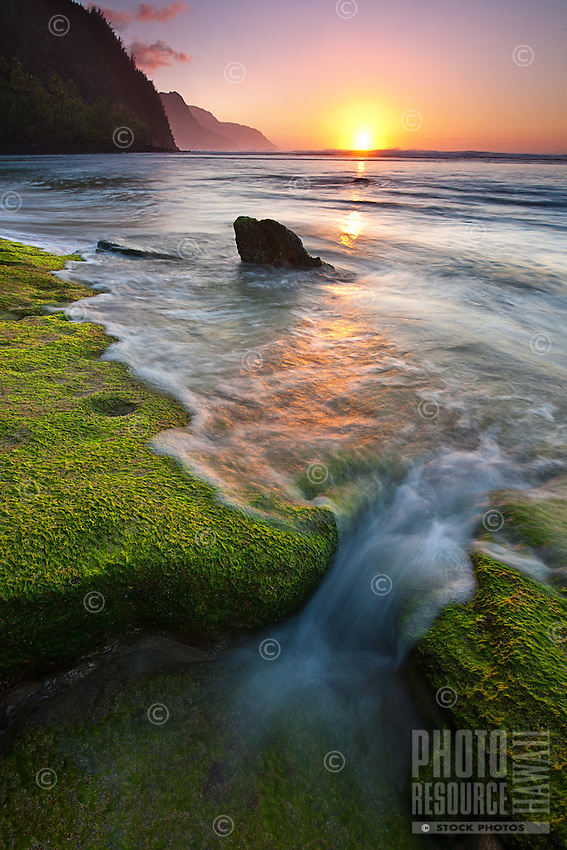 At sunset, a wave rushes over algae-covered rocks at Ke'e Beach, Kaua'i.