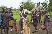 "Ethiopia. Southern Nations, Nationalities, and Peoples' Region. Omo Valley. Mursi tribe. Village and huts. Agro-pastoralist group. Nomadic. A group of Mursi women and children. Mursi women are known as ""disk-lip"" women. The bottom lip is slit along its full length and the front bottom row of teeth are pulled out to accomodate the ceramic disk which is handmade with a rim around which the stretched lip is pulled. The women are famed for wearing large plates in their lips (round clay plates placed into a cut in the lower lip) and ears. The disk is seen as a symbol of beauty and wealth, and often the younger girls will pierce and strech their ear-lobes, inserting a matching disk in the extended lobe. The Omo Valley, situated in Africa's Great Rift Valley, is home to an estimated 200,000 indigenous peoples who have lived there for millennia. Amongst them are 8'000 Mursi who dwell between the Omo and Mago rivers. Southern Nations, Nationalities, and Peoples' Region (often abbreviated as SNNPR) is one of the nine ethnic divisions of Ethiopia. 11.11.15 © 2015 Didier Ruef"
