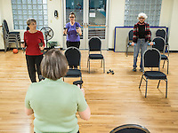 STAFF PHOTO ANTHONY REYES &bull; @NWATONYR<br /> Fink Holloway, bottom, leads Arlene Schuenemann, from left, of Fayetteville, Jean Greene, of Springdale, and Annette Williams, of Lowell, in the Strong Bodies program Tuesday, Dec. 23, 2014 at the Jones Center in Springdale. The program promotes fitness for seniors. The Jones Center will soon start a Silver Sneakers program, where seniors can qualify through their insurance for a free fitness membership.