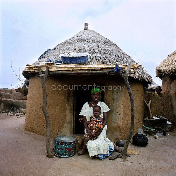 A woman with her child in front of her hut.