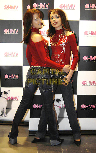 CHEEKY GIRLS.MONICA & GABRIELA IRIMIA.opening a new HMV store.November 2003.identical twins, full length, full-length, miss sixty denim jeans.www.capitalpictures.com.sales@capitalpictures.com.©Capital Pictures