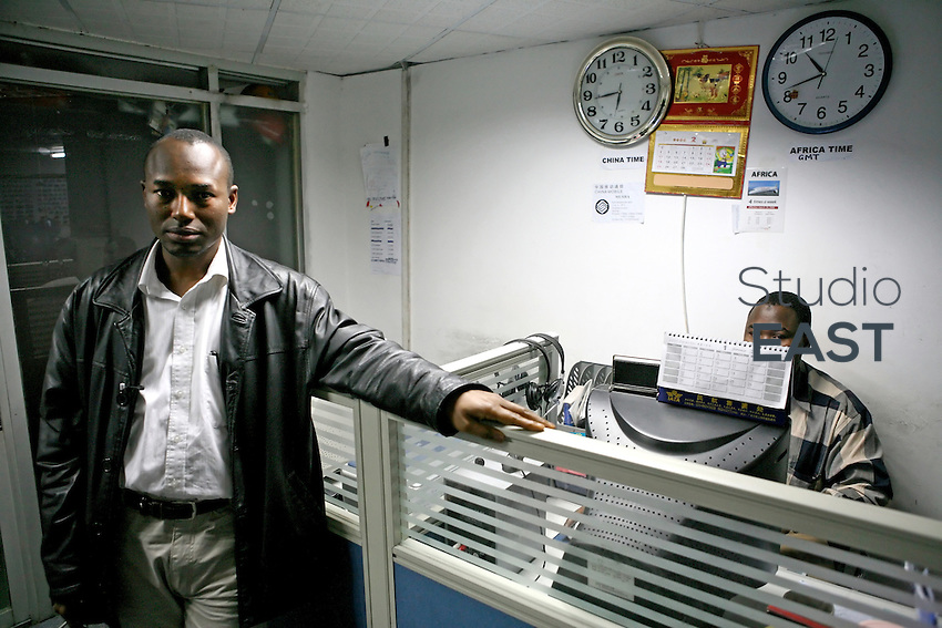 "Guinea-born businessman Mohammed Ali Diallo, left, poses in his offices, in Guangzhou, China, on March 15, 2007. Diallo, based in Guangzhou since 2006, says he ""found in China the cheapest products to export to the African market"". Chinese goods flow to Africa, but men flow the other way: thousands of Africans are now settling in China. China's Southern metropolis Guangzhou has the country's largest African population, now exceeding 7,000. Photo by Patrick Wack/Pictobank"