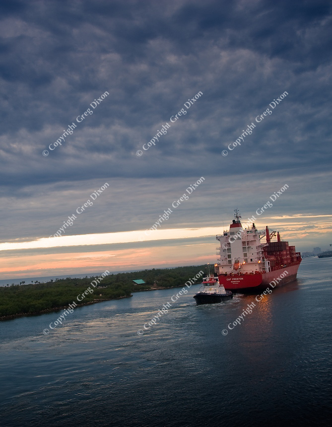 A tug boat tows a cargo vessel by a peninsula of Florida mangroves, as we approach the port of Fort Lauderdale on Feb. 11, 2012