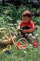 Child playing with garden vegetables in backyard with baskets of carrots, tomatoes, peppers, etc, squirrel statue ornament, lawn grass, in overalls