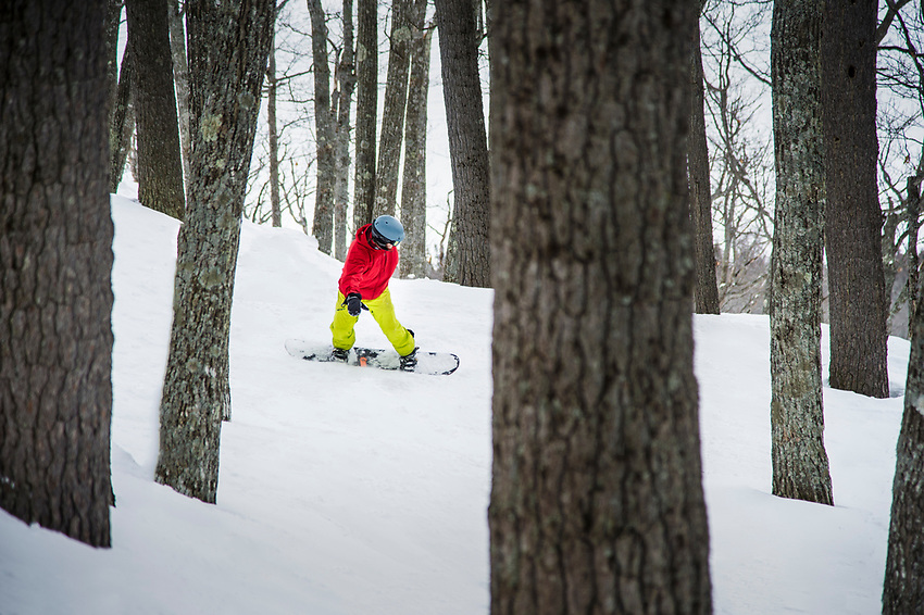 A snowboarder explores the gladed tree skiing at Mount Bohemia on Michigan's Keweenaw Peninsula.