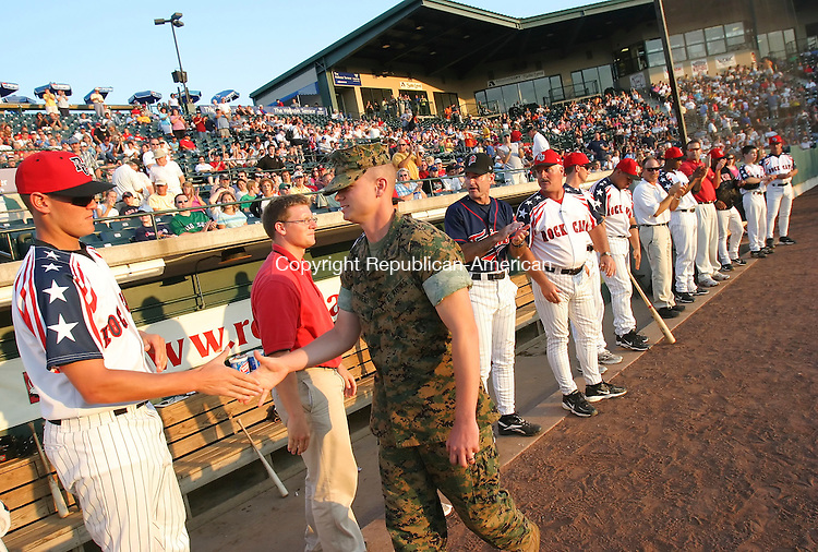NEW BRITAIN,  CT 10 August 2005 -081005BZ16- Former New Britain Rock Cats shortstop and current Marine Cpl. Tony Stevens shakes hands with current Rock Cats players after being honored for his military service before the game Wednesday.<br /> Jamison C. Bazinet Photo