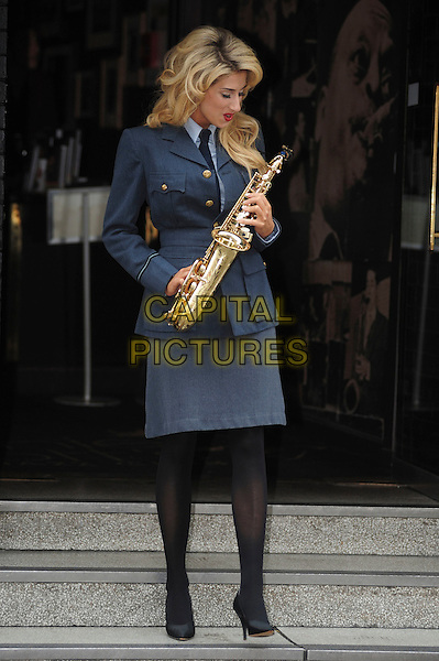 STACEY SOLOMON .The Royal Air Force Squadronaires - photocall at Ronnie Scott's Jazz Club, London, England UK, 11th June 2010..full length holding sax saxophone blue navy uniform military skirt jacket grey gray tights shoes black tie looking down funny .CAP/DYL.©Dylan/Capital Pictures.