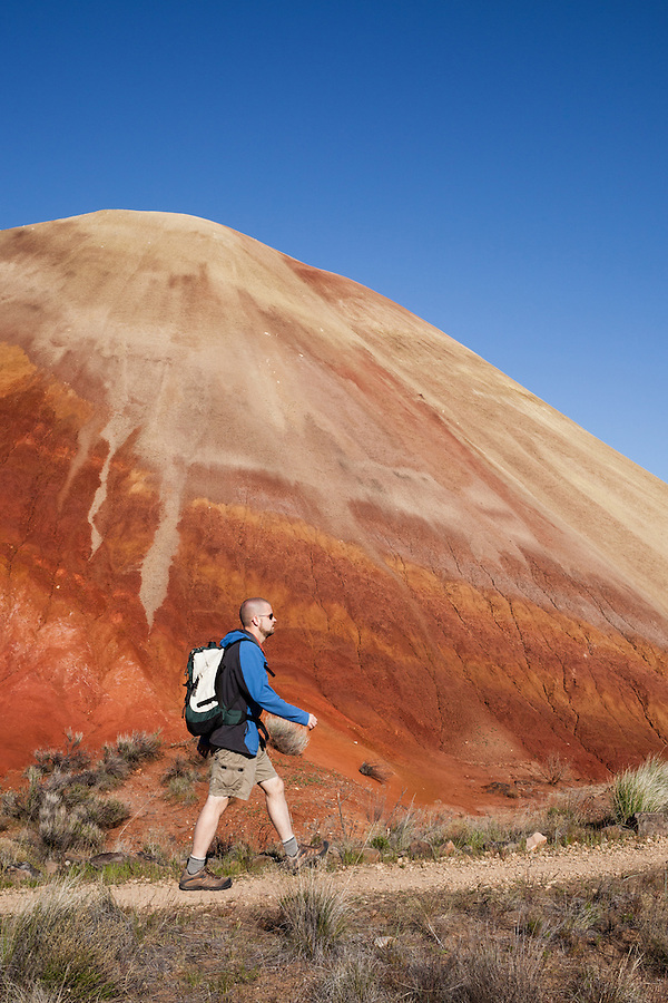 A man in his 30's wearing sunglasses hikes along a red hill in the Painted Hills section of the John Day Fossil Beds National Monument in Wheeler County, Oregon.