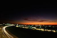 DAYTONA BEACH, FL - FEBRUARY 1: A time-exposure photo illustrating streaks of headlights as cars drive through the tri-oval near sunrise during the 1987 24 Hours of Daytona at the Daytona International Speedway in Daytona Beach, Florida, on February 1, 1987.