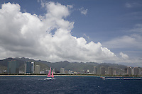 Sailboat and motor boat cruising off the coast of Honolulu, with mountains in the background
