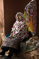 An elderly woman selling colorful fabric on the street in Abyaneh, Iran.